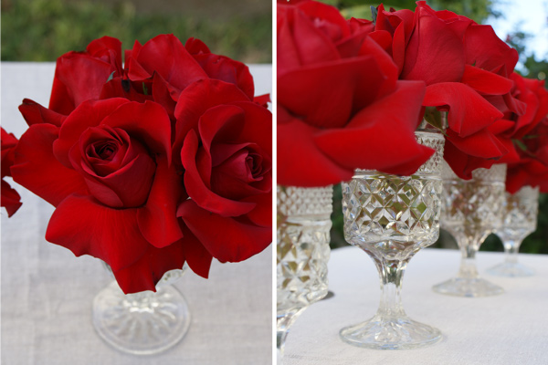 The centerpieces of reflexed silky red roses inside vintage wine glasses